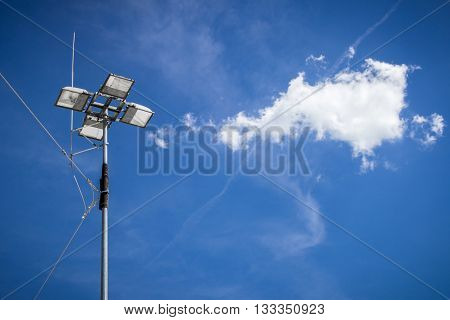 Industrial floodlight with blue sky background and clouds