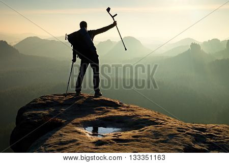Hiker with  medicine crutch above head achieved mountain peak. Broken leg fixed in immobilizer Deep misty valley bellow silhouette of man with hand in air. Spring daybreak