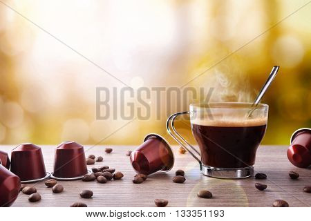 Cup Of Coffee With Capsules And Bainas And Local Background