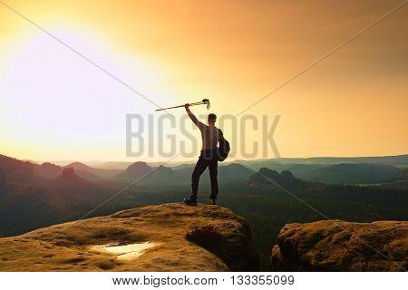 Hiker On Peak. Man In His Target With Poles In Hand In Air