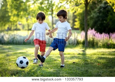 Two Cute Little Kids, Playing Football Together, Summertime. Children Playing Soccer