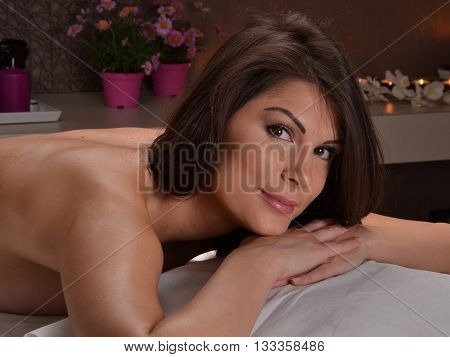 Beautiful latin woman portrait lying down on bed at beauty center spa. Looking at camera.
