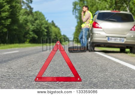 Man in reflective vest standing near broken car and calling to a car assistance. Focus on red triangle warning sign.