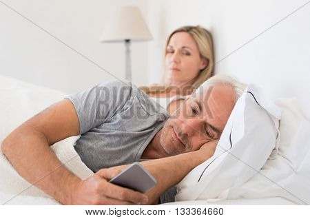 Jealous woman spying her husband mobile phone while he is reading a message. Senior couple in bed while wife is angry as husband using smartphone. Husband ignoring wife and texting on smartphone.