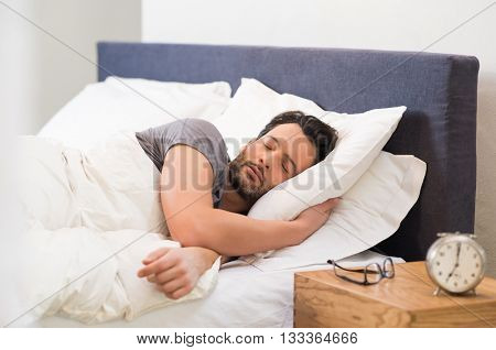 Handsome man sleeping in his bedroom. Man sleeping with alarm clock in foreground. Serene latin man sleeping peacefully.