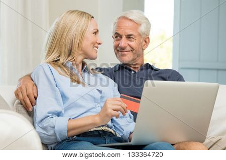 Happy senior couple making an online purchase. Mature couple making bookings online using credit card on their laptop. Smiling woman with her husband doing online payment with credid card.