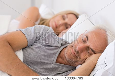 Senior man and woman sleeping. Senior man and woman resting with eyes closed. Mature couple sleeping together in their bed.