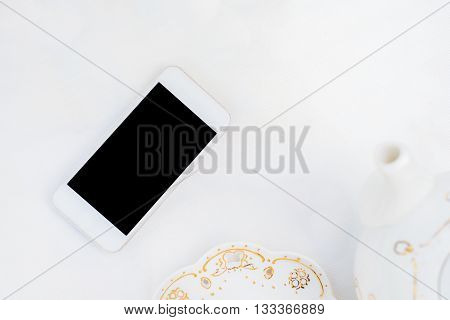 Styled white desktop with modern phone black screen.