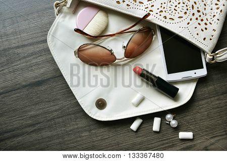 trendy handbag with woman´s treasures and secrecy