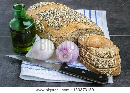 Whole wheat bread and rye sprinkled with sunflower seeds poppy seeds sesame seeds on a napkin next to the onion and olive oil bottle on a dark background