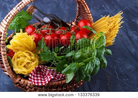 Italian food pasta ingredients, basil, tomato, olive oil, parsley, cheese, in a basket on dark background