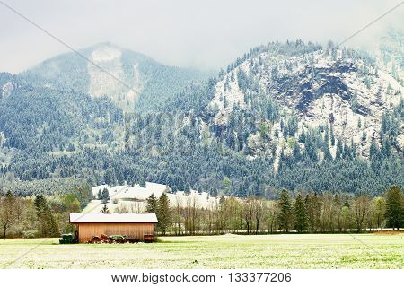 Barn Of Farmhouse. Spring Snow In Meadows Bellow Mountains.