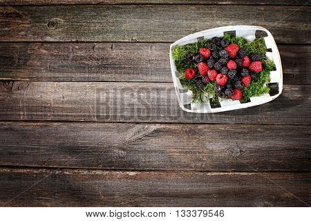 berries raspberries and blackberries in a basket on a wooden bacbackground