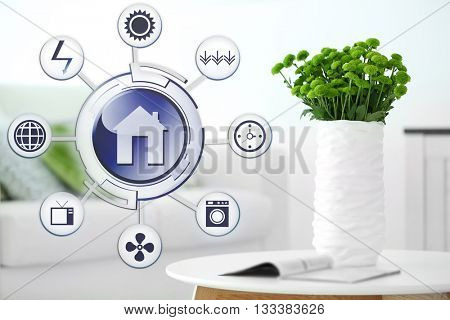 Smart home control concept. Room interior with sofa and vase with flowers on table