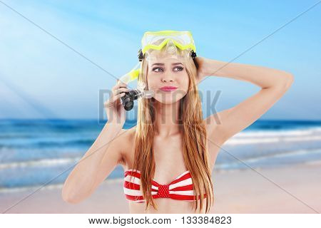 Young beautiful woman in red striped swimsuit and diving mask on blurred sea background