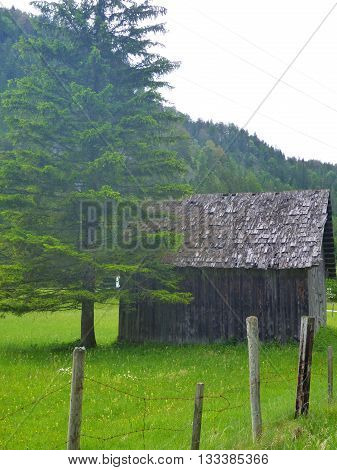 Small Wooden Hut On A Green Meadow