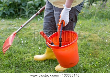 Woman With Gardening Equipment In Backyard