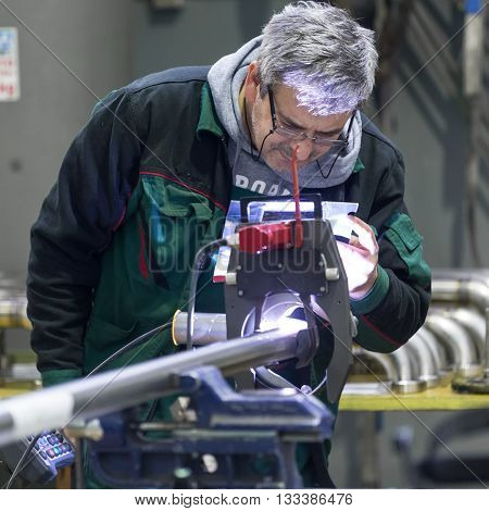 Industrial operator setting  computer controlled process of orbital welding machine in  stainless steel pipes manufacturing workshop. Square composition.