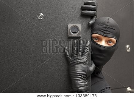 Ninja. Robber hiding behind a door with space for text