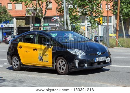 BARCELONA SPAIN - MAY 21 2016: Toyota Prius taxi driving through a street in Barcelona.