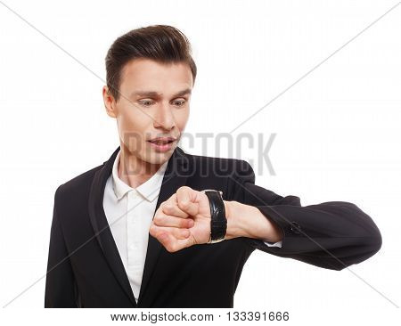 Hurry because he is running late. Businessman in a suit looking at wrist watch, isolated at white. Handsome, caucasian man checking time. Time is money, lack of time, unpunctuality concept.
