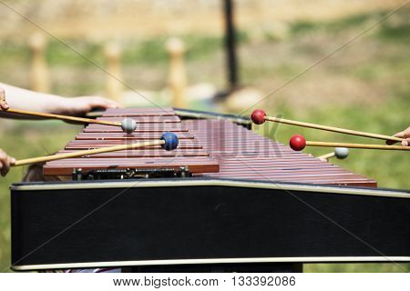 Xylophone with playing hands. Red xylophone for marimba. Music percussion instrument on grass background. Wooden xylophone with drumsticks. Wooden vibraphone with players hands. Hit to instrument keys