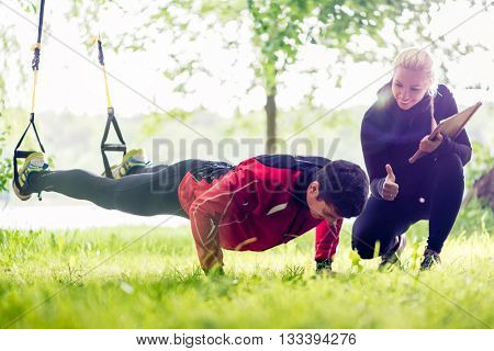 Sport couple outdoors with sling trainer