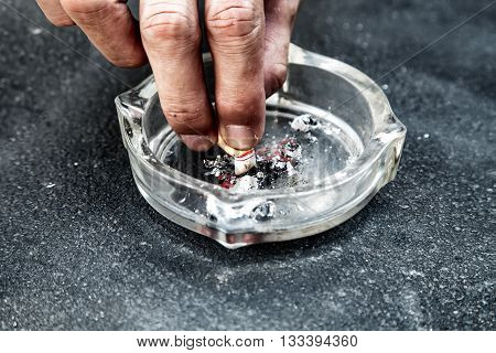 Hand With A Cigarette Butt Stubbed Out Amidst Ash, People Smoke Cigarette Look Like Trying To Commit