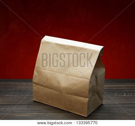 Brown kraft paper bag for lunch or food on wooden table at red background. Wrapping paper bag with copy space. Food bag for lunch or food take away delivery. Ecological natural bag.