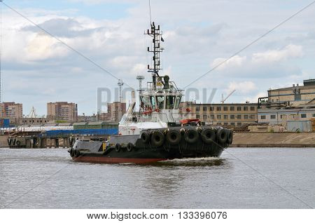 Russia.The port in St. Petersburg.The boat works in the port.He pulls a tanker from the berth after loading.