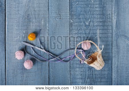 Yarn balls and basket. Knitwork background. Art craft, hand made. Handiwork, knitting, needlework. Wicker basket with woolen pink and orange balls at blue rustic wood background, top view, flat lay.
