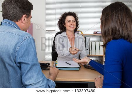 Confident Woman Realtor Giving Key Of New Apartment To Client.