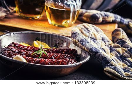 Sausage. Roasted chorizo sausage. Roasted spicy sausage chorizo home hotel or restaurant with beer vine brandy cognac whiskey. Still life. Toned photo.