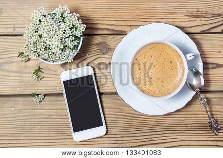 Vintage cup of coffee mobile phone and flowers on a wooden table.
