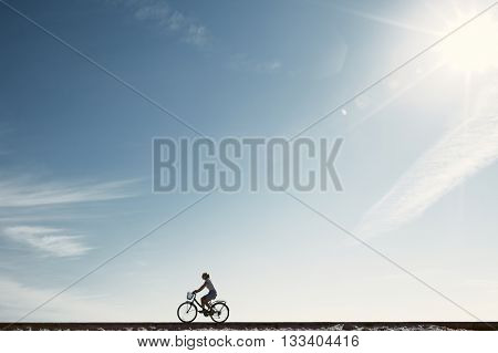 Silhouette of young woman riding old bicycle with basket against blue sky during summer vacation - healthy travel lifestyle concept