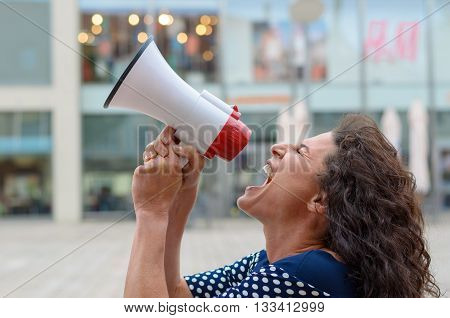 Young Woman Protester Shouting Into A Megaphone