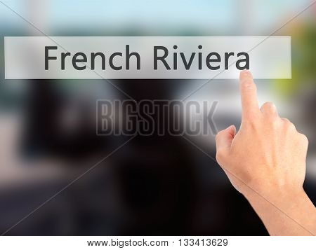 French Riviera - Hand Pressing A Button On Blurred Background Concept On Visual Screen.