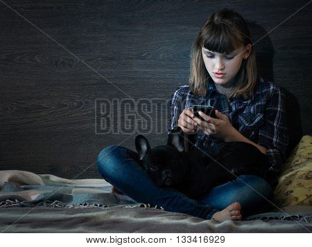 Teen girl sitting in the dark, on a bed with a mobile phone. On lap dog. The night is dark.
