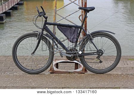 Locked Bicycle With Chain and Padlock at Pole