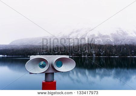 Sightseeing binoculars overlooking lake and mountain view in St. Moritz