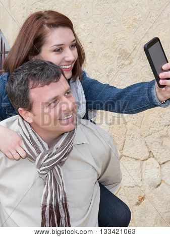 Man Giving Piggy Back To His Girlfriends And Taking Selfie