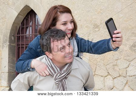 Tourist Man Giving Piggy Back To A Girl And Taking Selfie
