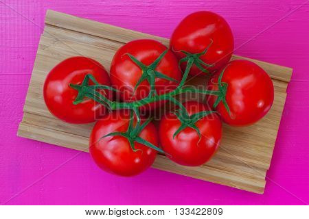 Six red tomatoes on the wooden desk