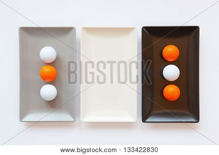 Different ceramic dishes with golf balls on over white background rectangle dish