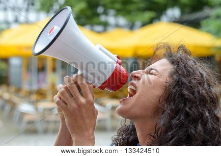 Angry young woman using a loud hailer or megaphone outdoors in an urban square during a protest or demonstration
