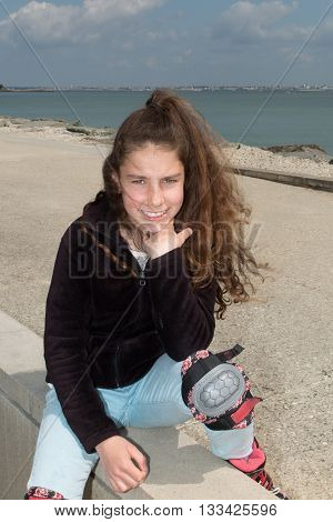 Fashionable teenager girl sitting on the wall at beach while roller skating. Recreational technology lifestyle outdoors.