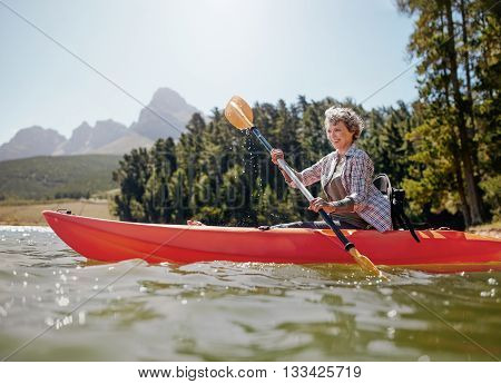 Shot of senior woman kayaking on lake on a summer day. Mature woman paddling a kayak in lake.