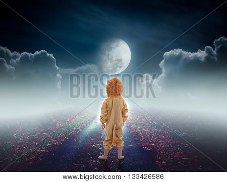 Back view of child costumed like a lion on pathway with a nightly sky and a large moon for halloween background. The moon taken with my own camera no NASA images used.