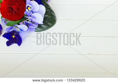 Posy of fresh violets, pansies and ranunculus on white wooden planks background with copy space