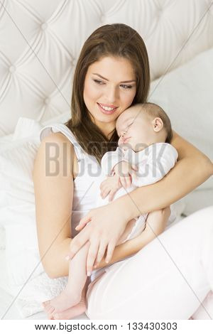 Happy mother with baby on bed  in the room